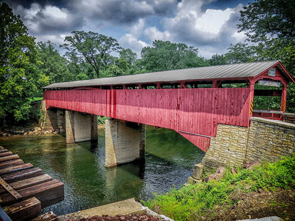 red covered bridge over quiet river. Gay roof and limestone piers, green trees and cloudy sky behind, portion of ties of railroad bridge in foreground