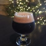 Footed round glass of dark beer with creamy head on counter with lighted Christmas tree in background
