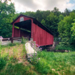Sam Eckman Covered Bridge - approach to red covered bridge with green grassy area in front and trees behind