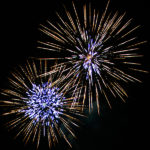 Two sunburst fireworks with blue white centers and gold streamers against night sky