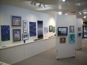 art gallery hung with blue paintings on white walls with greybrown carpet