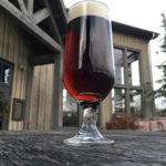 Footed glass of St Abbans Irish Red Ale with creamy head on rough wood table with rustic building behind