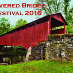 Red covered bridge with stone wall approach in foreground, green grass, trees in background Text: Covered Bridge Festival 2016