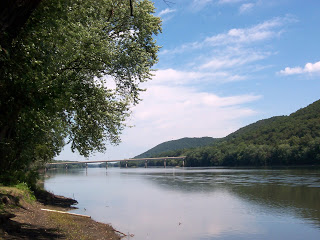 view along side the Susquehanna River with mountains of trees on the side and bridge over passing in the distance