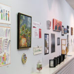 Over 20 art works in different media hanging on white wall