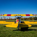 Vintage Steerman yellow bi-plane with red & yellow striped wings on grassy airfield
