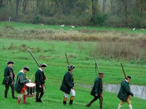 5 soldiers dressed in Revolutionary War uniforms with rifles on shoulders marching in a line on green grass