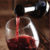 closeup of neck of wine bottle pouring red wine into glass