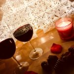 diagonal of two glasses of red wine, chocolates, burning candle in red holder, rose petal on wood table with white geometric background
