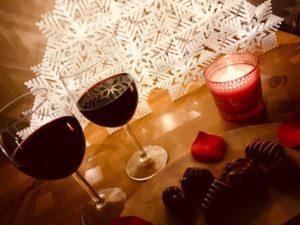 two glasses red win, chocolates, candle in red holder at angle