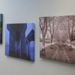 Three art works on grey wall - one seascape one blue architectural elements one sepia allee of trees