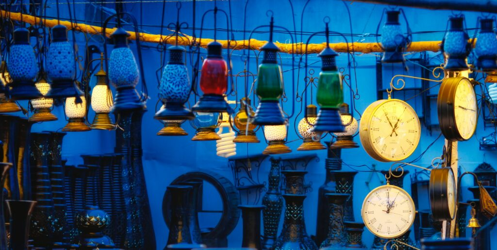 Antique lanterns hanging outside in the evening with an overall blue hue.