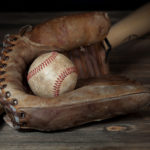 Dirty baseball nested in brown baseball glove with bat at angle behind on wooden surface