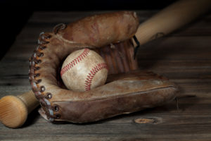 Dirty baseball nested in brown baseball glove lying against bat at angle behind on wooden surface