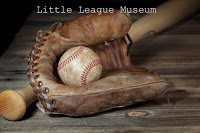 Old brown baseball mitt with dirty baseball inside, lying against wooden bat on gray wooden boards White text: Little League Museum