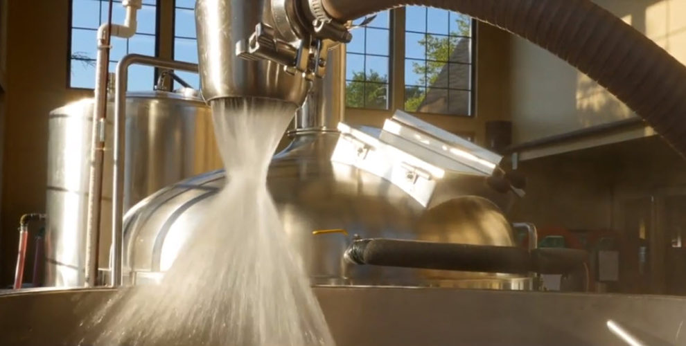 brewery equipment with white foamy liquid flowing downward amd staom;ess tank and window in background