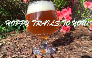 footed glass of beer with creamy head on brown mulch ground, pink flowers and green foliage behind Text: Happy Trails to You!