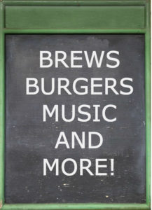 green framed blackboard with white chalk text: Brews Burgers Music and More!