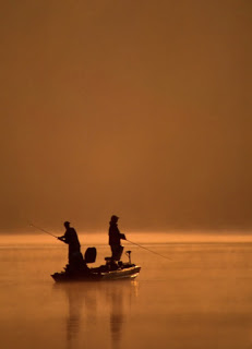 sepia silhouette of two fishermen standing in small boat on still lake with dark sky behind