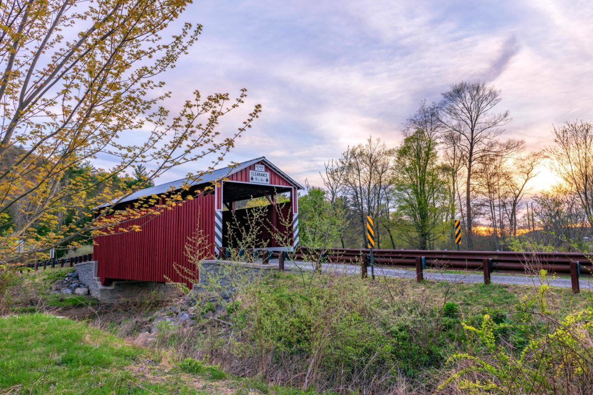 Kramer Covered Bridge in summer - red bridge with brown wood guardrails along road leading to bridge - trees surrounding and blue sky with clouds