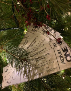 4 tickets to Brewmaster's Dinner fanned out against christmas tree with white lights