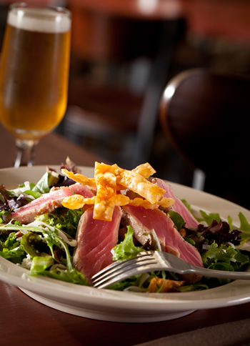 close up of acai tuna salad with glass of beer poured and served for guest to enjoy