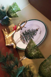 gold reindeer on shelf in front of china with christmas tree design and green glass goblets