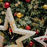 closeup of christmas tree decorated with large white stars and smaller gold and red balls
