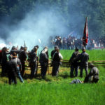 Civil War re-enactors standing behind wood rail fence firing volley with white smoke rising over green field