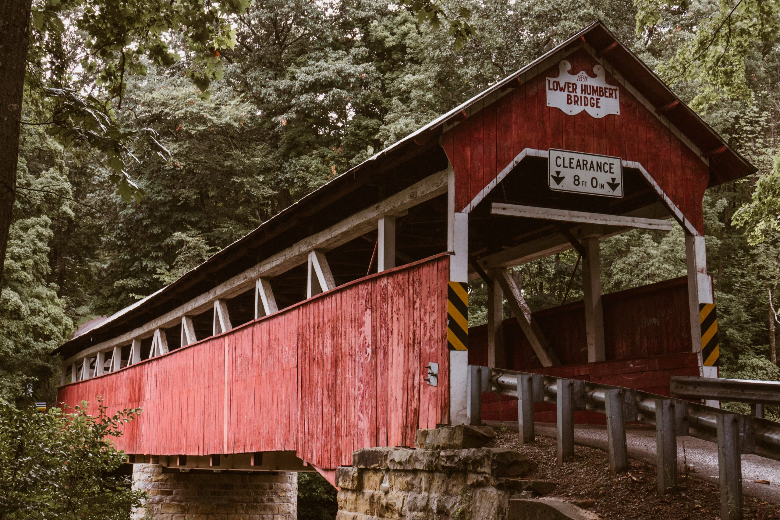 A red, one-lane covered bridge surrounded by green trees.