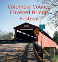 road leading into red covered bridge over river with traffic signs to right Text: Columbia County Covered Bridge Festival