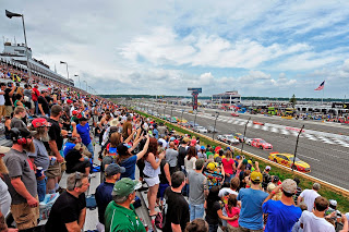 crowd standing in the stands along racetrack as they watch cars speed by