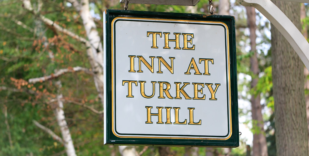 "hanging white sign with gold and green borders - etched with ""The Inn at Turkey Hill"" in gold lettering and green borders"