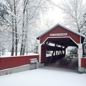 entrance to east paden red covered bridge with snow covered deciduous trees behind