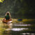 woman with long blond hair and green backpack paddling yellow kayak away on lake surrounded by green trees