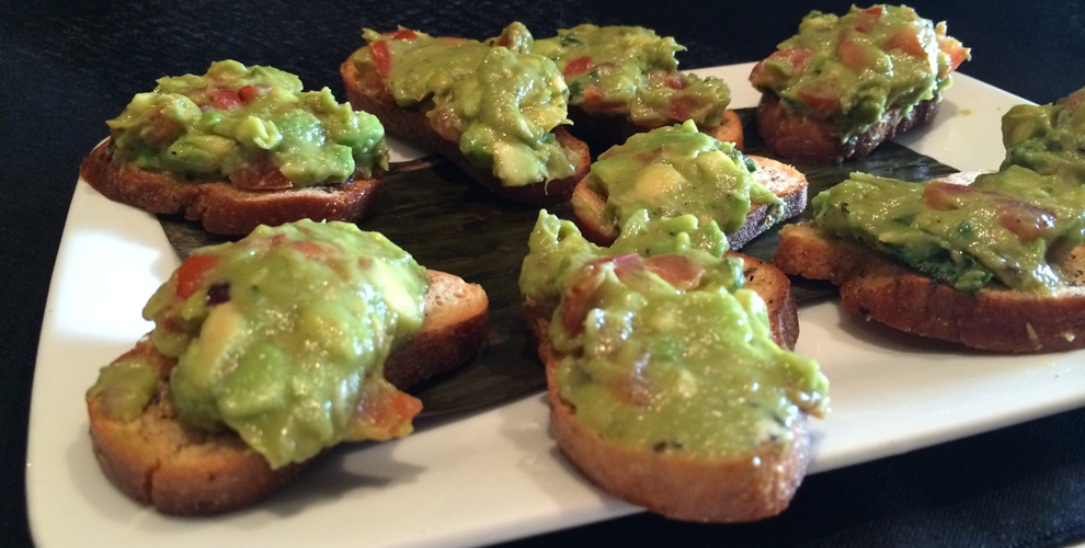 delicious fresh made guacamole placed on bread arranged on plate for serving