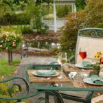 glass topped table with wine glasses and bottle & green chairs on patio in flower garden with gazebo in background