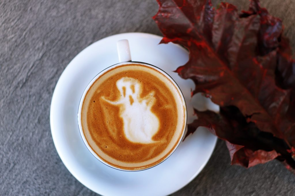 white ceramic teacup filled with ghost illustration coffee latte on white ceramic saucer beside maroon leaf