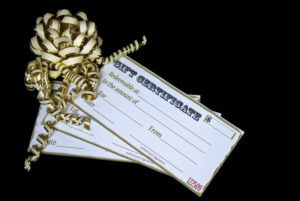 stack of 3 gift certificates tied with gold ribbons on black background