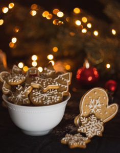gingerbread snowflakes and stars with white icing in white bowl christmas lights behind