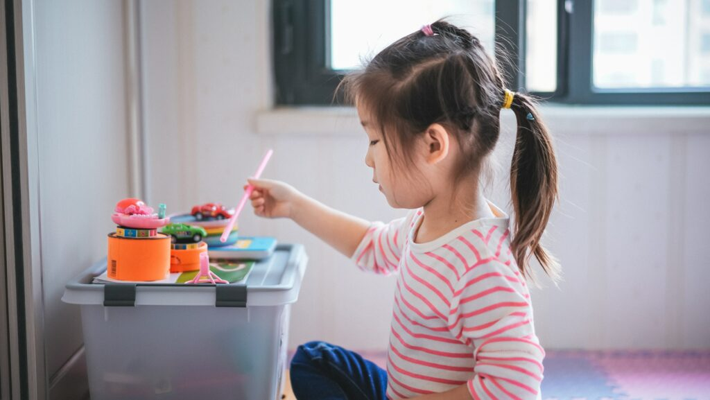 A girl in a pink striped shirt sits and plays with toys.
