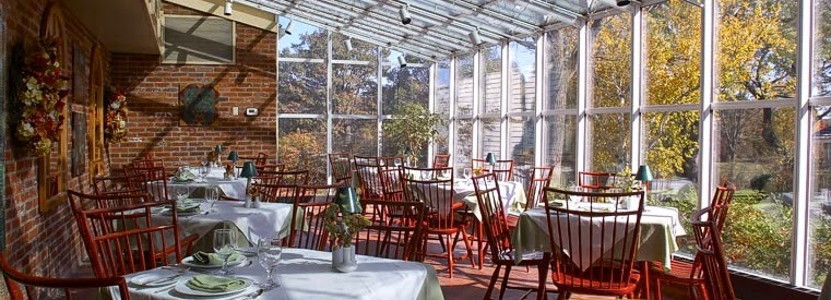 display of our restaurant green house room looking through glass windows on one side and brick on the other with tables set between for guests to arrive and enjoy fine dining