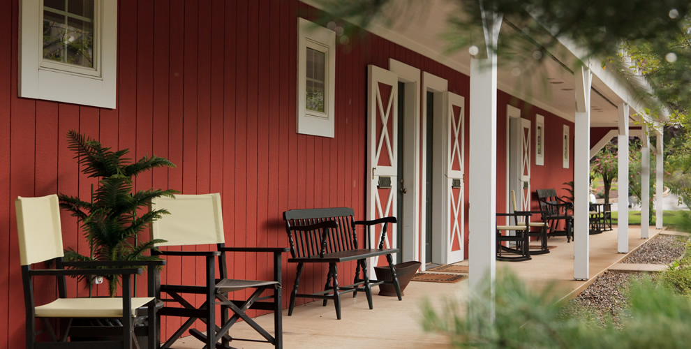 side view of the outside of stable rooms - red vertical wood sides complimented with barn doors (red with white 'x' through them) with white pillars surrounded porch/front area - many chairs placed for relaxation and seating outside to enjoy weather