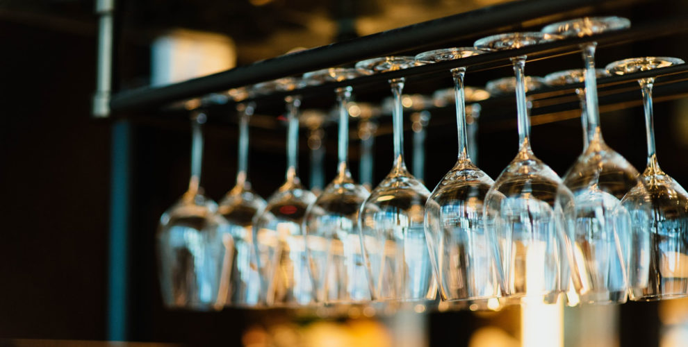 two rows of clear wine glasses hanging upside down over bar