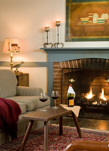 couch next to fireplace with two wine glasses set and poured on table