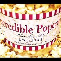 "red and white bucket of buttery popcorn says ""Incredible Popcorn"""