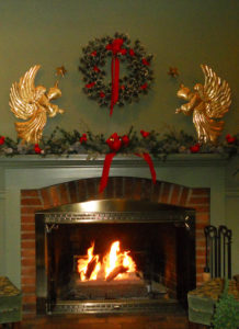 blazing fireplace with christmas mantel decorations of wreath, garland with white ribbons, and white tree branches with red cardinals