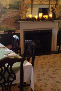 dining table with green and white tablecloths and antique chairs, white fireplace with christmas angels decoration