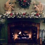 holiday decorations of two gold angels, wreath and evergreen garland with white lights on mantel