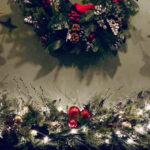 holiday decorated mantel with 2 gold angels facing central wreath, greens with white lights & red balls on mantel